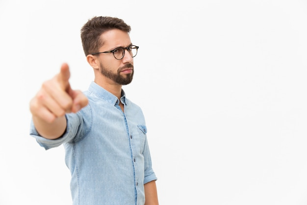 Strict frowning guy in eyewear pointing finger Free Photo