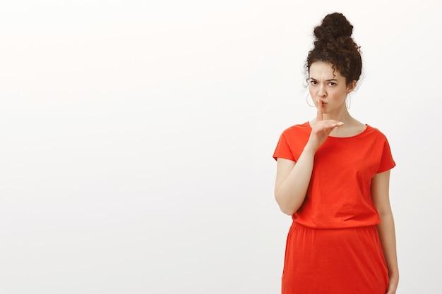 Строгая симпатичная кавказская женщина с кудрявыми волосами в повседневном красном платье говорит: «тсс», предупреждающе жестикулирует, прикрывая рот указательным пальцем, хмурясь. Бесплатные Фотографии