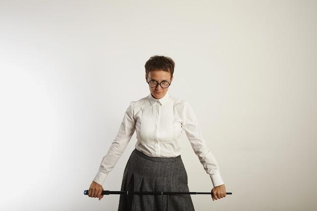 白い壁に長い黒のポインターを持つ厳格な外観の保守的な服装の女教師 無料写真