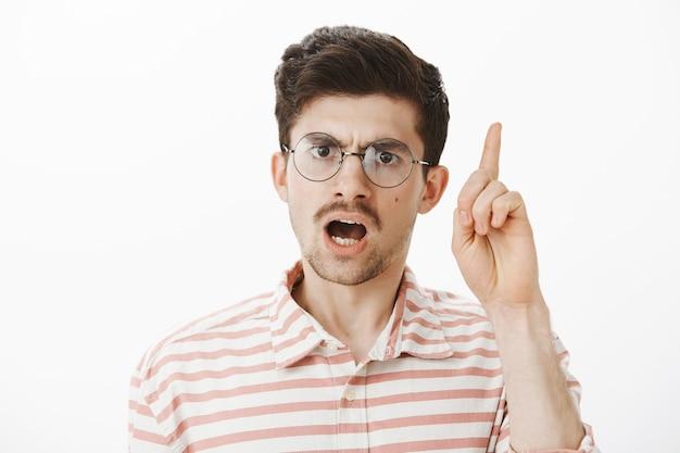 Строгий учитель ругает учеников за плохое поведение. снимок серьезного сосредоточенного бородатого мужчины с усами, поднимающего указательный палец, выступающего и спорящего, недовольного стоящего над серой стеной Бесплатные Фотографии