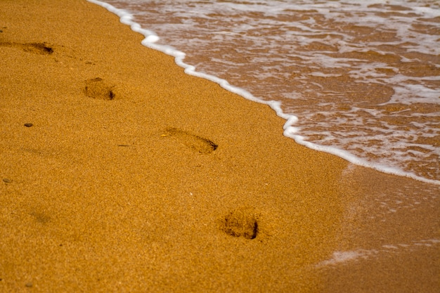 A string of bare footprints in the sand. waves on the sea coast, sandy beach. foam on sea water. Premium Photo