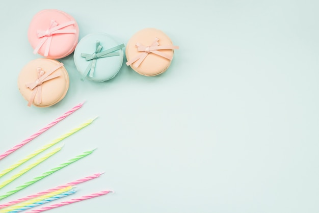 Striped candles and macarons with bow on white background Free Photo