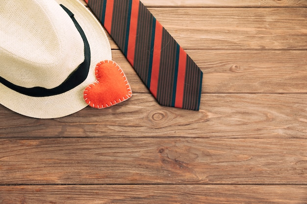 Striped tie near hat and heart on board Free Photo