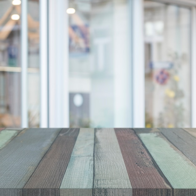 Striped wooden table in front of glass window Free Photo