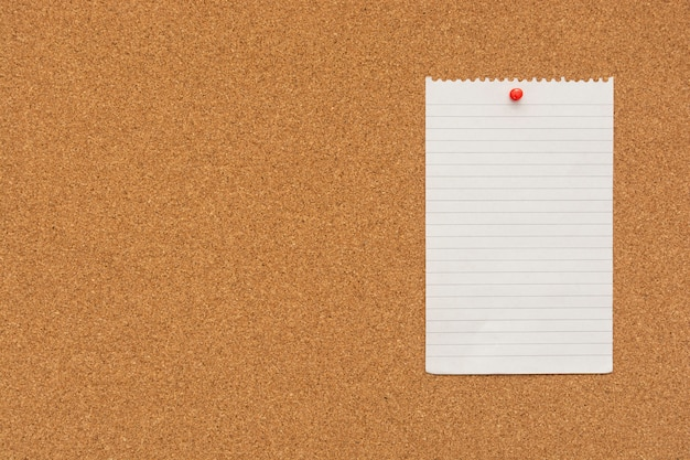 Stripped note paper with push pin on cork board Premium Photo