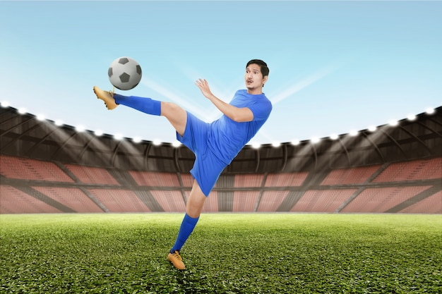 Strong asian soccer player kick the ball Premium Photo