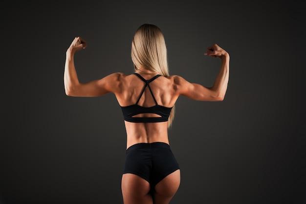 強い運動女性フィットネスモデル、背中の筋肉をポーズ Premium写真