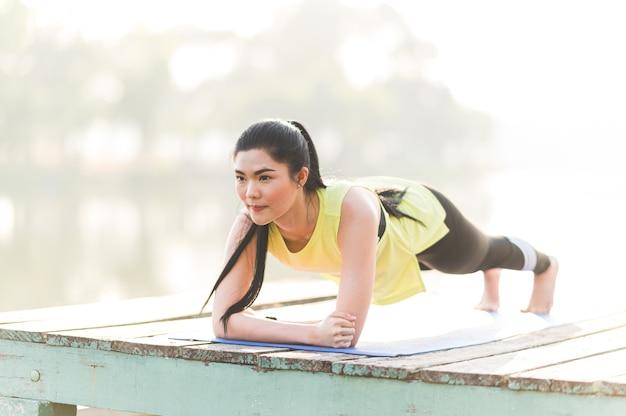 板張りのコア筋肉運動を行う強力な美しいフィットネス屋外、健康的なライフスタイルとダイエットの概念 Premium写真