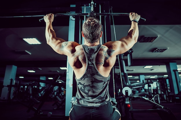 Strong bodybuilder doing heavy weight exercise for back on machine Premium Photo