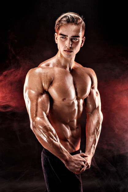 Strong bodybuilder man with perfect abs, shoulders, biceps, triceps, chest posing in smoke hands up. Premium Photo