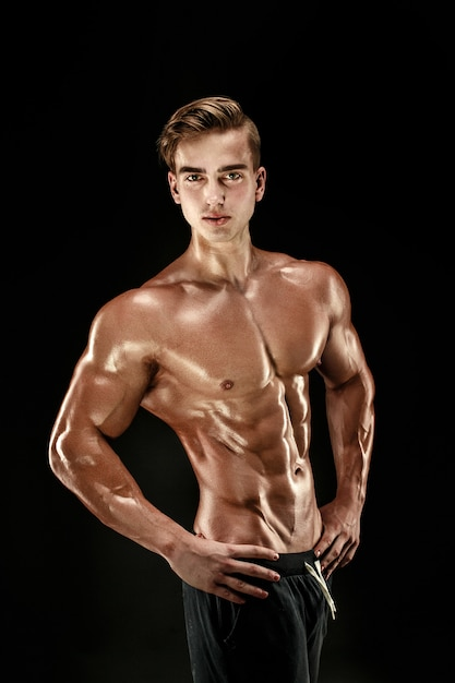 Strong bodybuilder with six pack, perfect abs, shoulders, biceps, triceps and chest Premium Photo