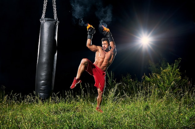 Strong boxer punching sandbag outdoors Premium Photo