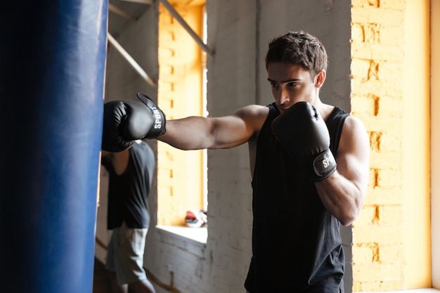 Strong boxer training in a gym. Free Photo