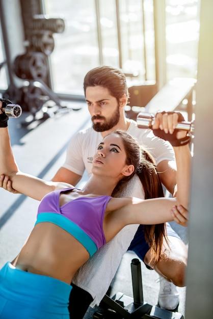 여성 고객이 체중 운동을 올바르게 할 수 있도록 돕는 강력한 개인 피트니스 트레이너. 프리미엄 사진
