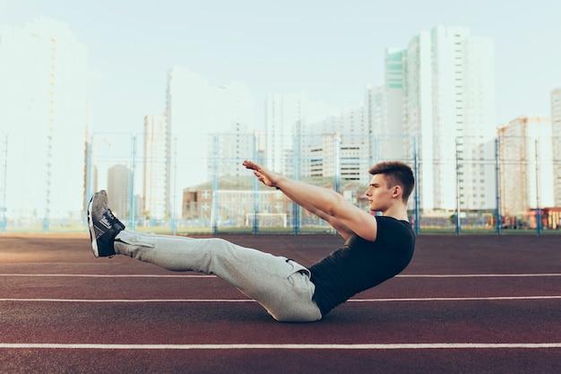 Сильный парень с хорошим телом утром на стадионе. он носит спортивную одежду, занимается спортом. он выглядит напряженным. Бесплатные Фотографии