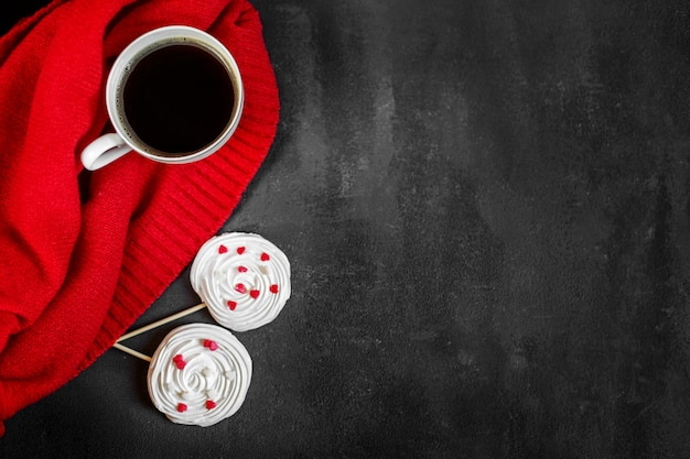 Strong hot coffee and french meringue on a red background. concept of drinks, leisure and lifestyle. Premium Photo