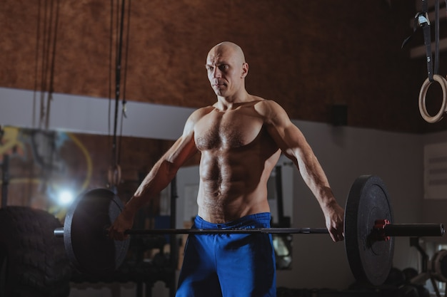 Strong male crossfit athlete exercising with heavy barbell Premium Photo