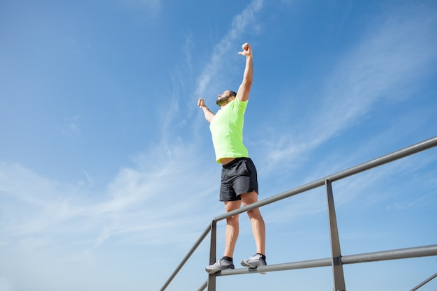 Strong man celebrating sport success outdoors Free Photo