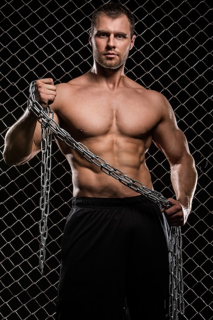 Strong man on fence with chains Free Photo