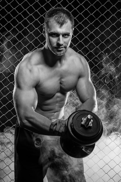 Strong man on fence with dumbbell Free Photo