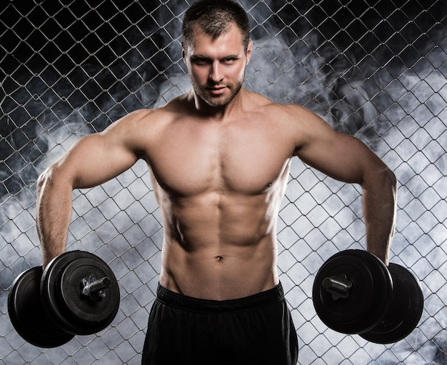 Strong man on fence with dumbbells Free Photo