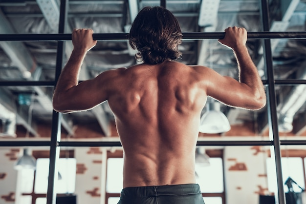 A strong man performs pull-ups on the bar. Premium Photo
