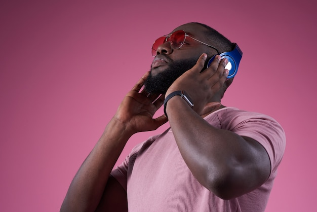 Strong man presses the headset closer to the head.. Premium Photo
