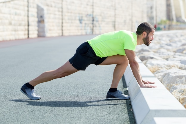 Strong man stretching calf and leaning on curb Free Photo