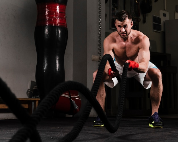 Strong man training hard for boxing competition Free Photo
