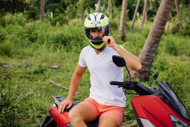Uomo forte sul campo della giungla tropicale con moto rossa Foto Gratuite