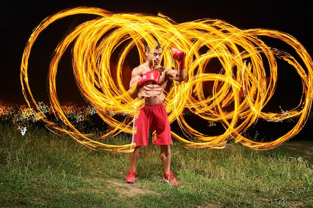 Strong muscular male fighter posing with fire and flames Premium Photo