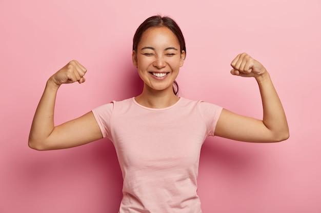 濃い櫛の髪、歯を見せる笑顔、腕を上げて上腕二頭筋を見せ、耳にピアスをし、カジュアルなバラ色のtシャツを着て、ピンクの壁にモデルを付けた、強くてパワフルなアジアの女性。私の筋肉を見てください! 無料写真