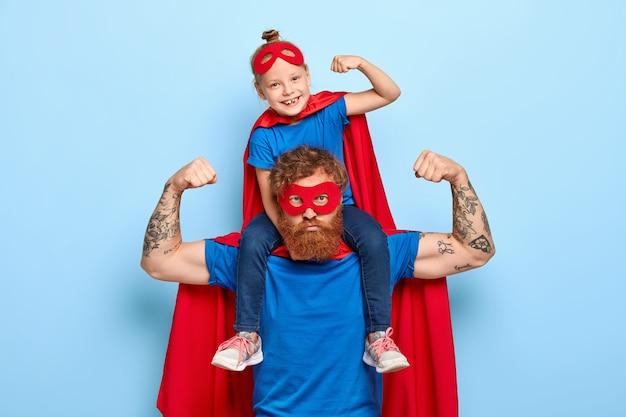 강력한 강력한 아빠와 그의 어깨에 작은 여자 아이가 근육을 보여줍니다. 무료 사진
