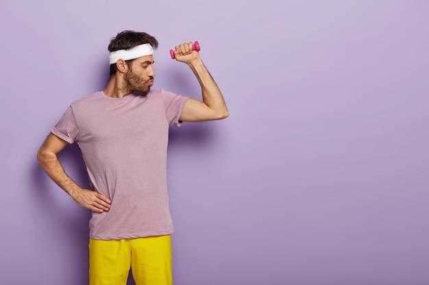 太い剛毛を持ち、カジュアルな服装で、片手を腰に当て、ダンベルでエクササイズをし、定期的なトレーニングを楽しんでいる強力で強力な男性 無料写真