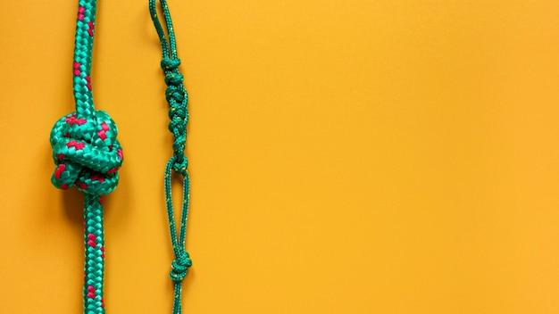 Крепкие веревочные узлы копируют пространство на желтом фоне Premium Фотографии