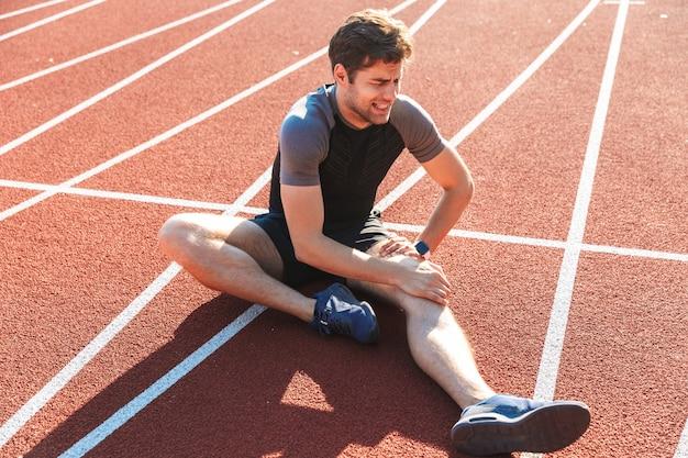 Сильный спортсмен страдает от боли в колене Premium Фотографии
