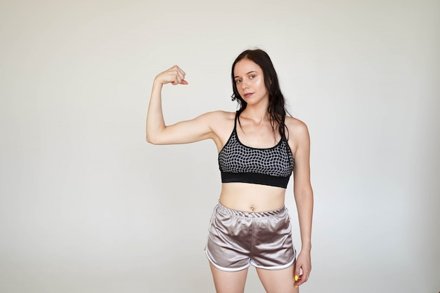 Strong sporty girl in sports top and panties showing demonstrating arms muscules on white background with copy space Premium Photo