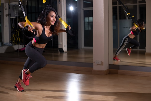 Strong woman doing trx exercise with straps in the fitness gym Premium Photo
