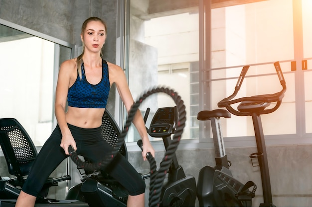 Strong woman exercising with rope in functional training fitness gym. Premium Photo