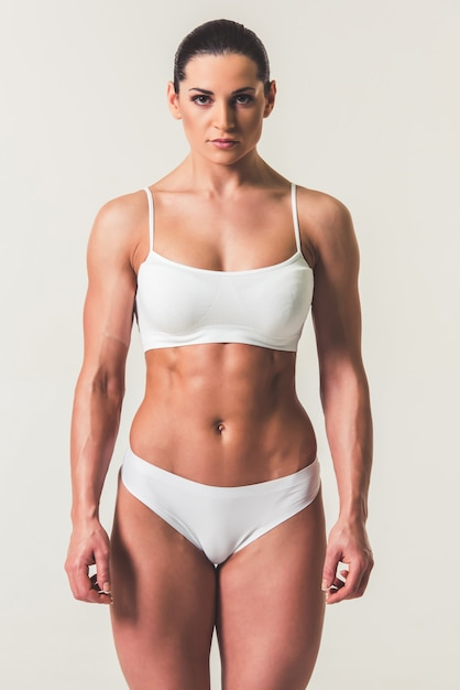 Strong woman in white underwear on light background Premium Photo