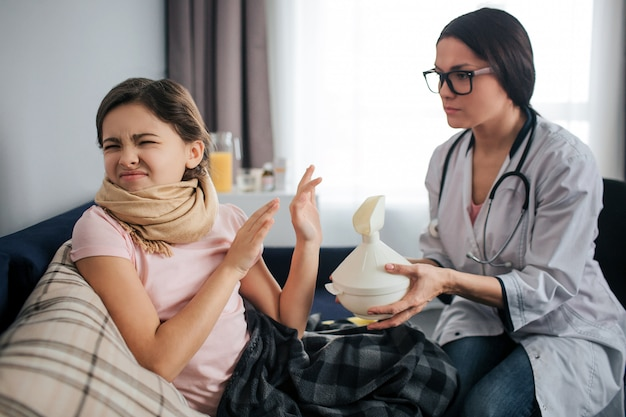 Stubborn sick girl shrink and keep eyes closed. she doesn't want to do inhalation procedure. female doctor hold white inhaler and give it to kid. they sit in one room. Premium Photo