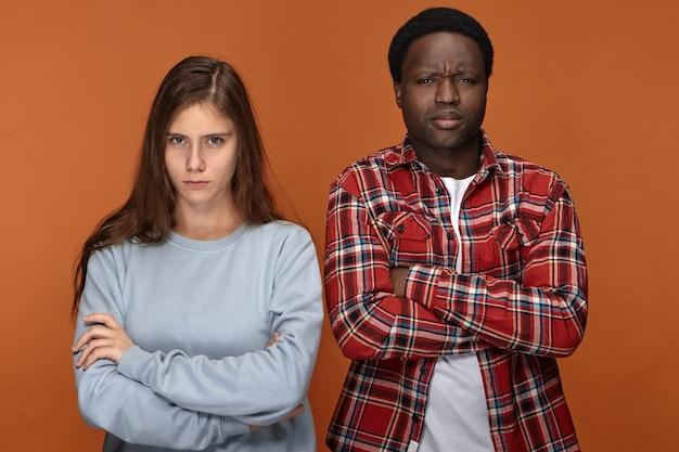 頑固な若い異人種間のカップルが週末の計画について不機嫌そうな表情で意見の相違を持ち、腕を組んだまま、眉をひそめ、お互いに話していません 無料写真