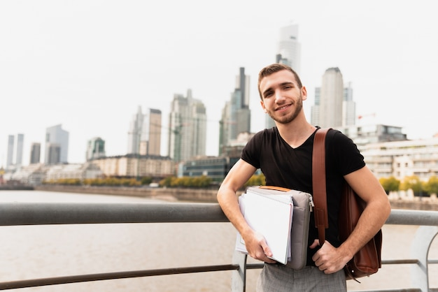 Student in a big city holding his notes Free Photo