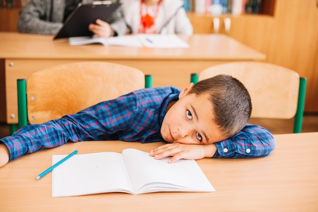 Student boy leaning on desk in classroom Free Photo