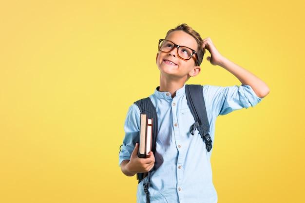 Студенческий мальчик с рюкзаком и очками стоит и думает об идее. обратно в школу Premium Фотографии