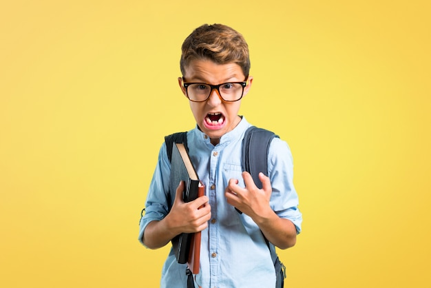 Student boy with backpack and glasses annoyed angry in furious gesture. back to school Premium Photo