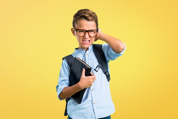Student boy with backpack and glasses covering both ears with hands. back to school Premium Photo