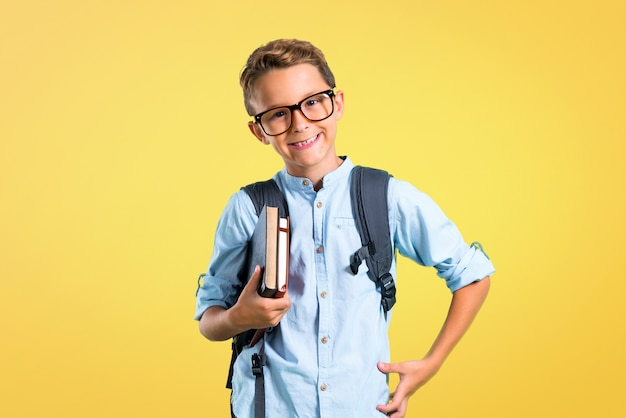 Student boy with backpack and glasses posing with arms at hip on yellow background. Premium Photo