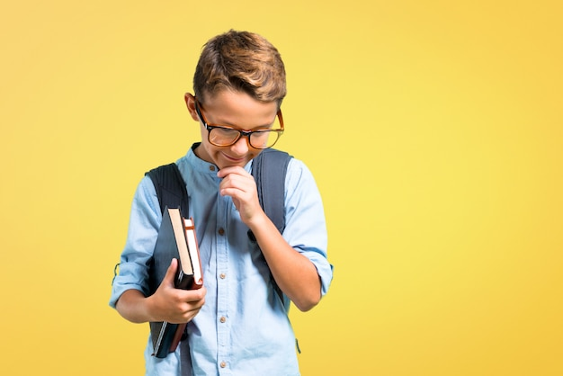 Student boy with backpack and glasses standing and looking down on yellow background. Premium Photo