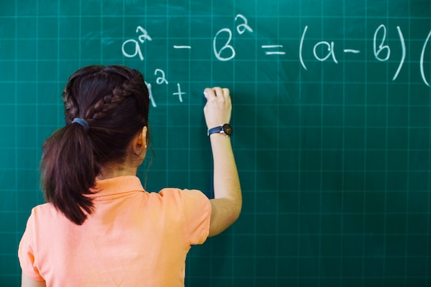 Student calculating on the blackboard Free Photo